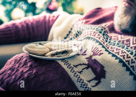 Man wearing sweater asleep with mince pies on chest - Stock Photo