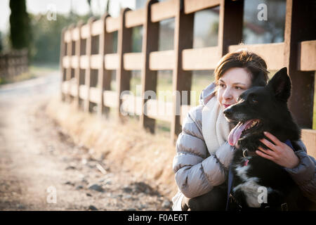 Portrait of mid adult woman with her dog on country lane - Stock Photo