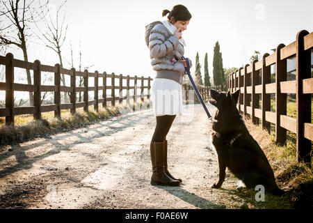 Mid adult woman training her dog to sit on rural road - Stock Photo