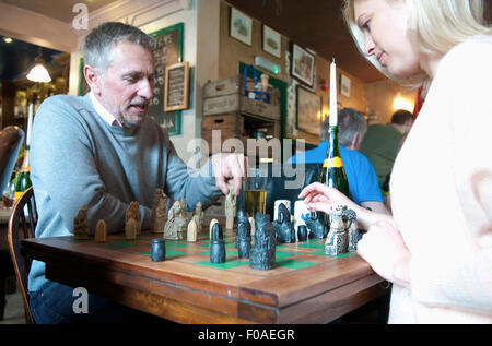 Couple playing chess in pub