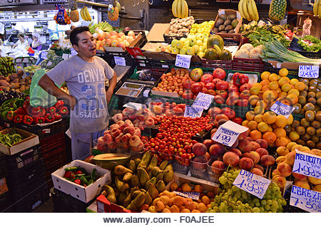 Cheerful shopkeeper at fruits and vegetables stall, La Boqueria market Ciutat Vella Barcelona Catalonia Spain Europe - Stock Photo