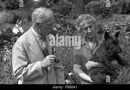 A couple with their Scottish terrier dog standing in a garden - Stock Photo