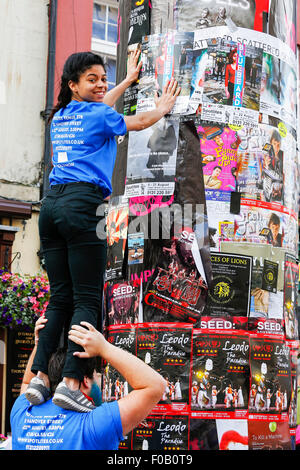 Rebecca Solomon from Spotlites theatre Group, standing on the shoulders of Lewis Colson, as she puts up adverts - Stock Photo