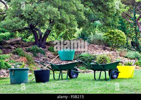 Garden tools, green barrows, buckets in garden with trees, shrubs and rocks - Stock Photo