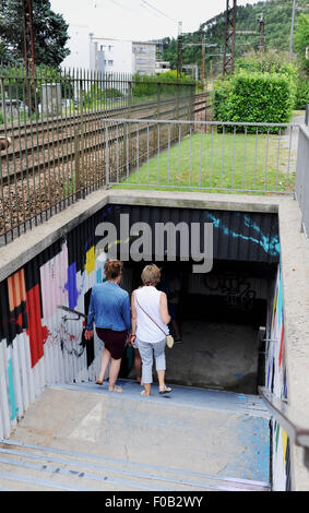Female tourists walk through an underpass to cross railway tracks at Cahors  the main town of the Lot Department - Stock Photo