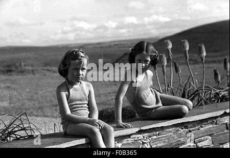 Two young girls in their bathing suits sitting on a garden wall - Stock Photo
