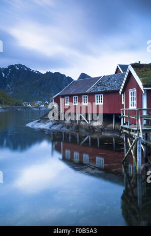 Red rorbu (fishermen's huts),in front of mountain, Reine fjord, Lofoten Islands, Norway, Europe - Stock Photo