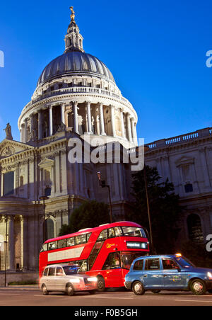 LONDON, UK - AUG 22, 2014: Red bus and taxi cabs in front of St.Paul's Cathedral just after sunset. - Stock Photo