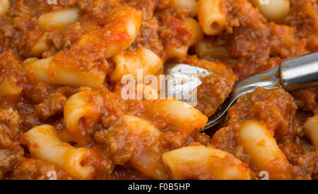 Close view of a microwaved beef and macaroni TV dinner with a spoon. - Stock Photo