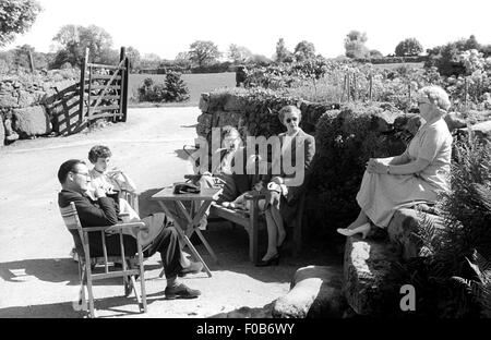 A group of smartly dressed people sitting outside in a garden of a house in the country. - Stock Photo