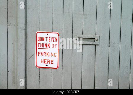 'Don't even think of parking here' sign on an old wooden garage door in Burford Cotswolds Oxfordshire England UK - Stock Photo