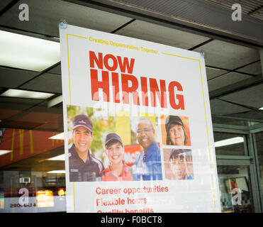 A sign in the window of a McDonald's in Chelsea in New York advises potential job applicants of the opportunities - Stock Photo