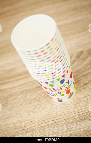 Stack of Happy Birthday paper cups with balloons and bunting image on the side - Stock Photo