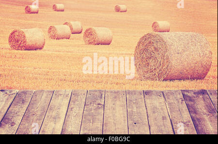 Vintage toned hay bales on a field with wooden boards. - Stock Photo