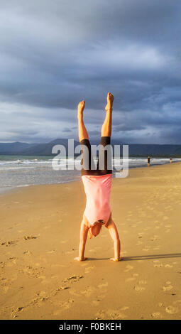 A young woman doing a handstand on beautiful tropical beach. - Stock Photo