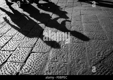 tourist walking up the cobblestone pavement of Florence, Italy - Stock Photo