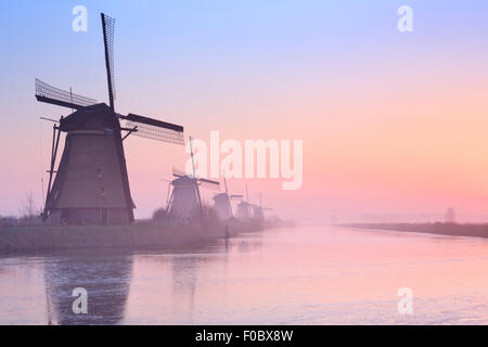 Traditional Dutch windmills on a cold morning at sunrise in winter, at the Kinderdijk in The Netherlands. - Stock Photo