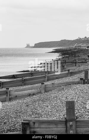 Groynes on Herne Bay Beach and Reculver Towers in the distance, Herne Bay, Kent, England, United Kingdom - Stock Photo