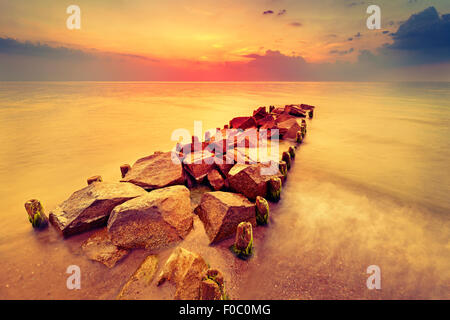 Beautiful sunset over beach and rocky pier. - Stock Photo