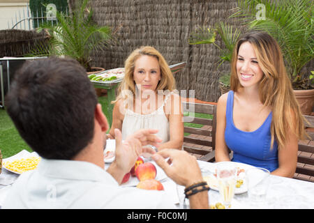 Elderly and younger woman listening to man during lunchtime - Stock Photo