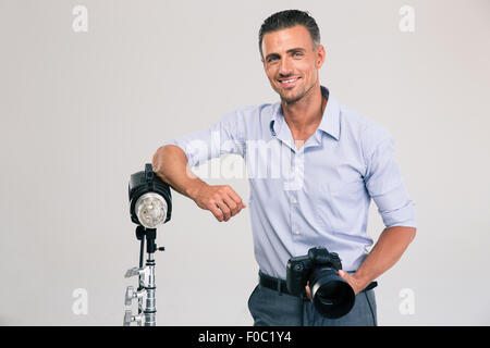Portrait of a cheerful young photographer standing with camera isolated on a white background and looking at camera - Stock Photo
