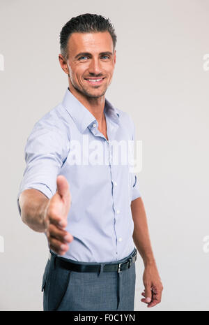 Portrait of a happy businessman stretching hand for handshaking on gray background - Stock Photo