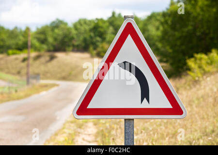 Triangular traffic sign indicating road is turning left on a rural road background - Stock Photo