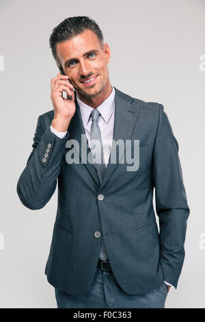 Portrait of a happy businessman talking on the phone isolated on a white background - Stock Photo