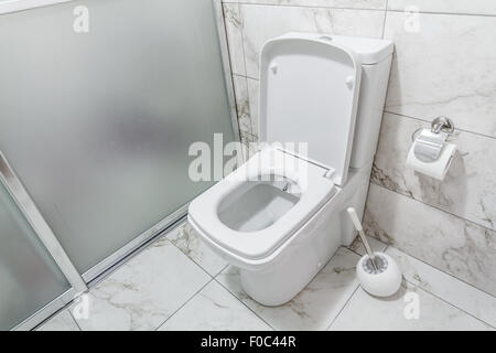 White toilet bowl in a bathroom with marble like ceramics - Stock Photo