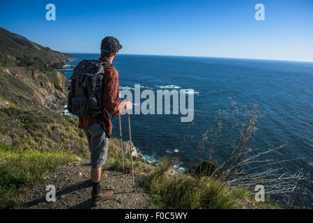 Young male hiker looking out from cliff top, Big Sur, California, USA - Stock Photo