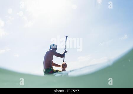 Low angle view of young man and toddler daughter paddleboarding - Stock Photo