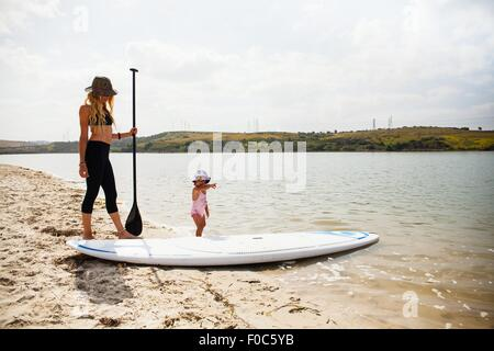 Mid adult woman and toddler daughter with paddleboard on beach, Carlsbad, California, USA - Stock Photo