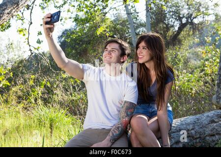 Young couple taking smartphone selfie in park - Stock Photo