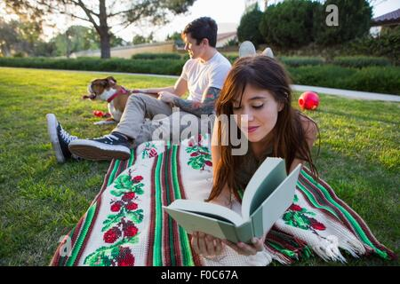 Young woman reading book whilst boyfriend pets dog in park - Stock Photo