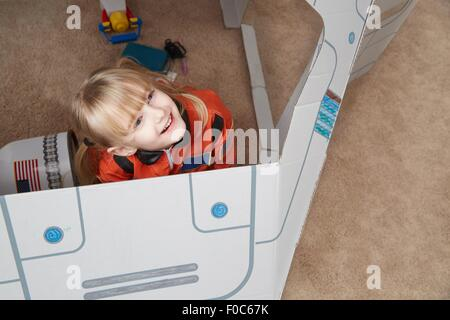 Young girl playing in cardboard spaceship, wearing astronaut outfit, elevated view - Stock Photo