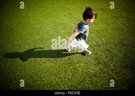 Boy with shadow running across the grass - Stock Photo