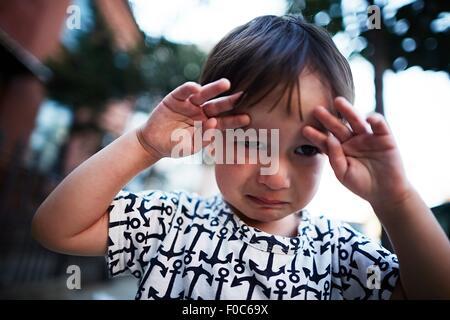 Portrait of boy crying on street - Stock Photo