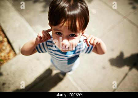Portrait of boy putting his fingers in his ears on street - Stock Photo