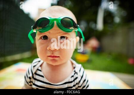 Close up portrait of baby boy looking at camera wearing swimming goggles - Stock Photo