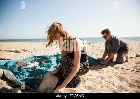 Couple setting up tent on beach, Malibu, California, USA - Stock Photo