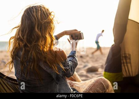 Woman taking photograph on beach - Stock Photo