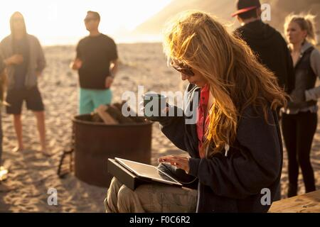 Woman using digital tablet on beach, friends in background - Stock Photo