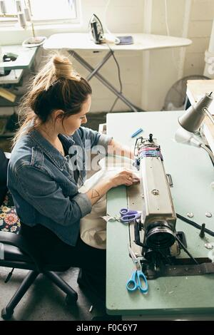 Female seamstress using sewing machine in fashion studio - Stock Photo