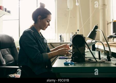 Young female seamstress using sewing machine in fashion studio - Stock Photo