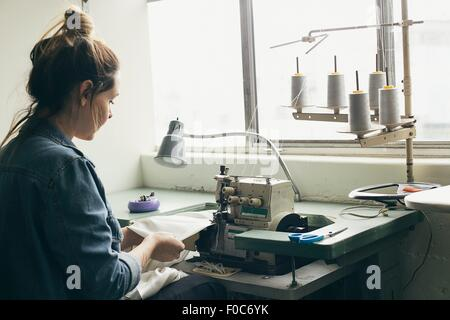 Young female seamstress sewing textile on sewing machine - Stock Photo