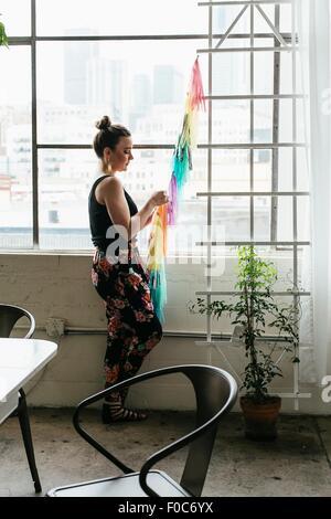 Young female designer making multi colored bunting in design studio - Stock Photo