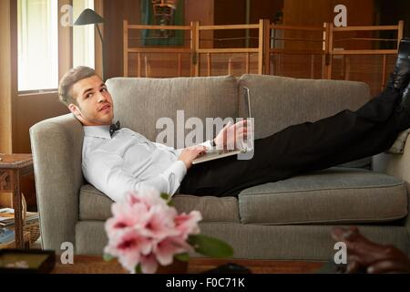 Portrait of man wearing smart clothes laying on sofa using laptop - Stock Photo