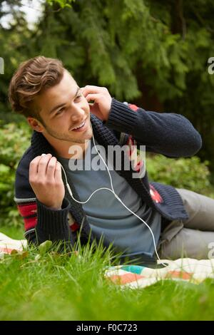 Portrait of man laying in garden listening to smartphone wearing earphones - Stock Photo