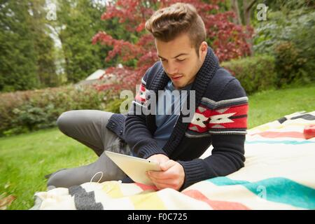 Portrait of man laying in garden reading digital tablet - Stock Photo