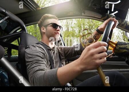 Portrait of man driving wearing sunglasses - Stock Photo